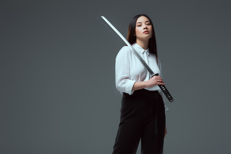 attractive young asian woman holding katana sword and looking at camera isolated on grey Stock Photo
