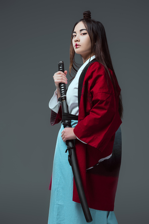 beautiful asian woman in kimono holding katana and looking at camera isolated on grey