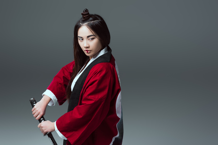 asian woman in kimono holding katana sword and looking away isolated on grey Banco de Imagens