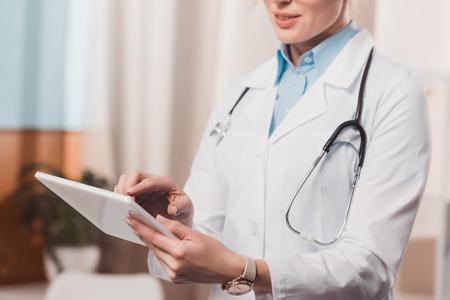 Vista parcial de la doctora con tableta en manos en la clínica
