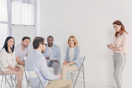 psychotherapist taking notes and working with multiethnic people sitting on chairs during group therapy Stock Photo