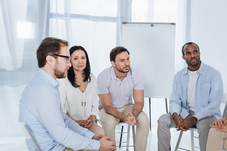 anonymous group of multiethnic middle aged people sitting on chairs during therapy Stock Photo