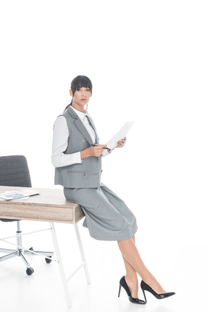 businesswoman leaning on table and holding documents isolated on white