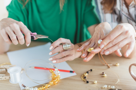 cropped shot of women making accessories of beads Stock Photo