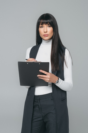 businesswoman standing with clipboard and looking at camera isolated on gray Stok Fotoğraf