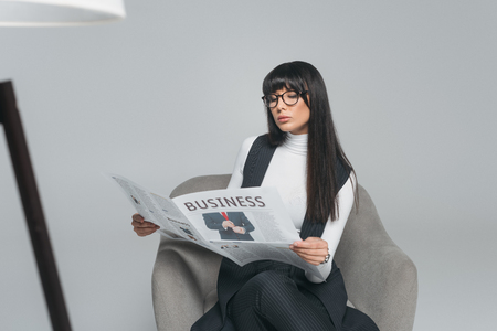 attractive brunette businesswoman reading newspaper isolated on gray Banco de Imagens