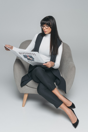attractive brunette businesswoman reading newspaper in armchair on gray
