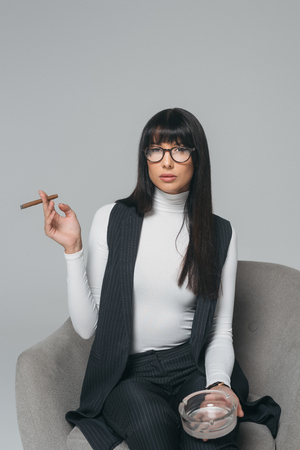 beautiful brunette businesswoman with ashtray and cigar isolated on gray