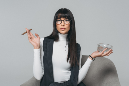 attractive brunette businesswoman holding ashtray and cigar isolated on gray