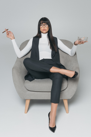 businesswoman holding ashtray and cigar and sitting in armchair on gray Banco de Imagens - 114820016