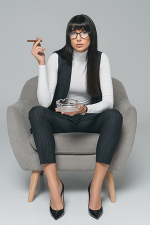 businesswoman smoking in armchair and looking at camera on gray Banco de Imagens