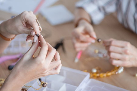 cropped shot of women making accessories of beads at workshop 스톡 콘텐츠 - 114821410