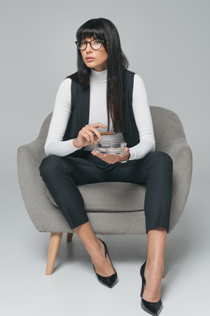 attractive brunette businesswoman holding ashtray and cigar on gray Banco de Imagens