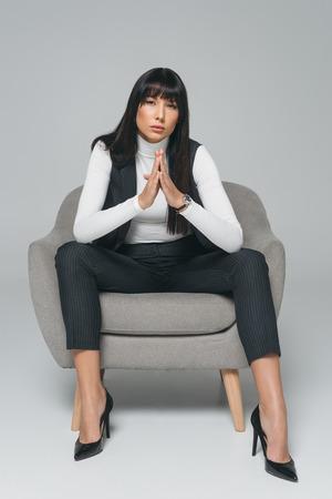 attractive brunette woman sitting in armchair on gray Banco de Imagens