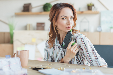 happy young woman having fun with glue gun in handmade workshop