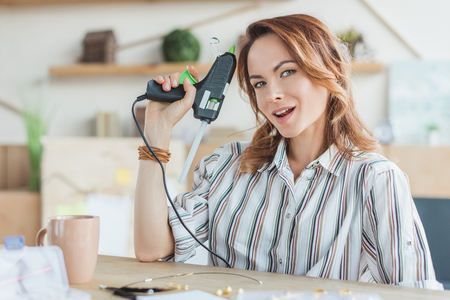 happy young woman with glue gun in handmade workshop Stock Photo