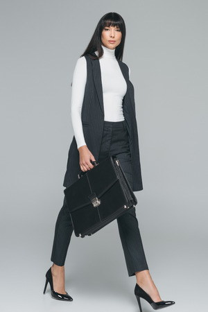 attractive brunette businesswoman walking with briefcase on gray Banco de Imagens - 114821437