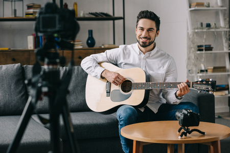 happy music blogger playing acoustic guitar