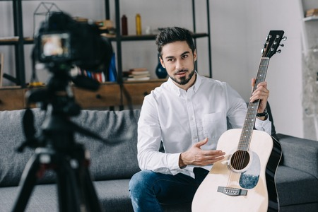 handsome music blogger holding and describing acoustic guitar