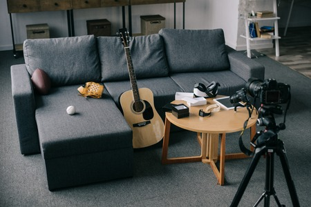 acoustic guitar and cameras with gray sofa in empty room