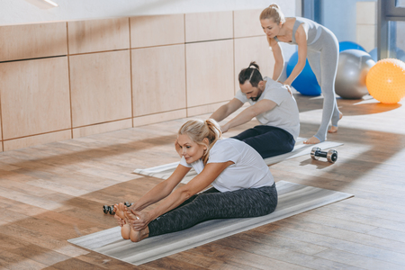 instructor helping mature people stretching on yoga mats in fitness studio