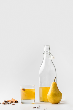 bottle of pear cider with cinnamon and anise on white
