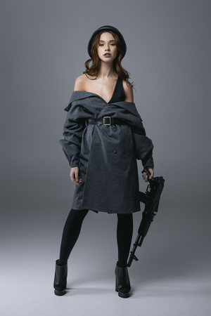 seductive beautiful woman posing in coat and military helmet with rifle, isolated on grey Banque d'images