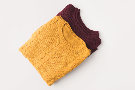 top view of knitted burgundy and yellow sweaters, isolated on white Stock fotó
