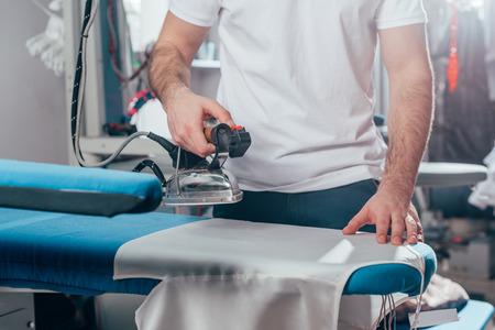 przycięte zdjęcie pracownika pralni chemicznej przy użyciu przemysłowego żelaza w magazynie Zdjęcie Seryjne