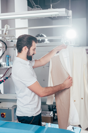 dry cleaning worker with white jacket on hanger