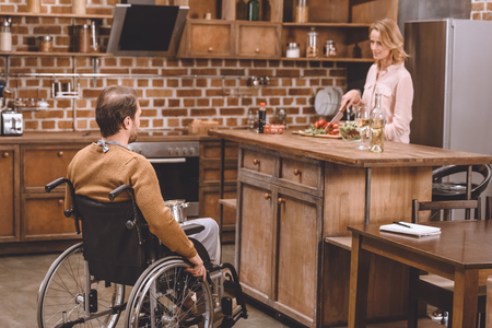woman with disabled man in wheelchair cooking dinner together at home Stockfoto