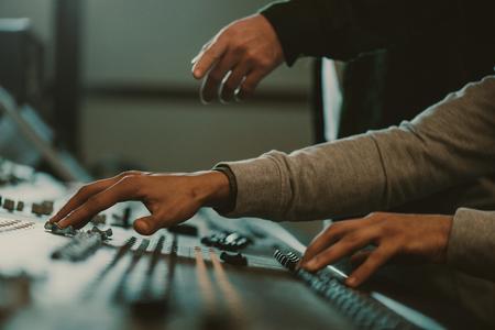 cropped shot of men using analog graphic equalizer at recording studio