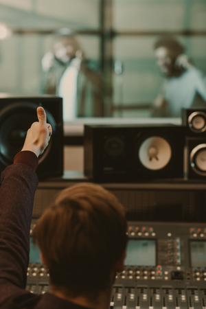 sound producer showing thumb up to singers behind glass at recording studio
