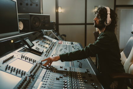 side view of concentrated sound producer working at studio Stockfoto
