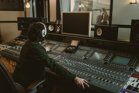 sound producer working at studio while recording song Banco de Imagens