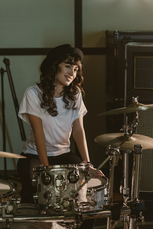 attractive female drummer sitting at drum set Фото со стока - 114550816