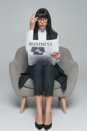 attractive brunette businesswoman reading newspaper on gray