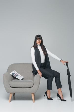attractive brunette businesswoman sitting on armchair with umbrella isolated on gray