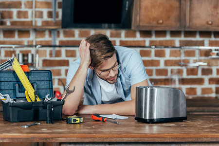 frustrated young man in eyeglasses looking at broken toaster at home Banque d'images - 114550670