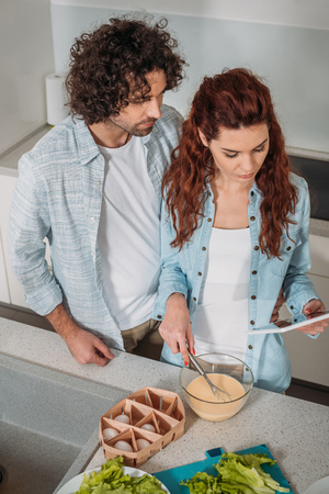high angle view of girlfriend preparing batter with recipe on tablet Stock Photo