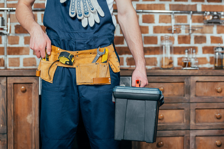 mid section of home master with tool belt holding toolbox Stock Photo