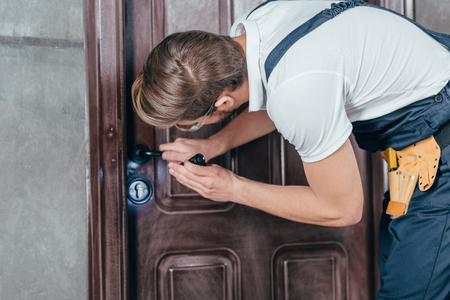 young manual worker in overall and goggles checking door lock with flashlight Banque d'images - 114550121