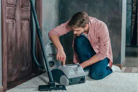 young man looking at broken vacuum cleaner and fixing it at home