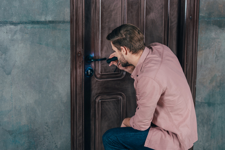 young repairman checking door lock with flashlight Banque d'images - 114550128