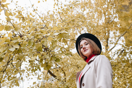 bottom view of young stylish woman in trench coat and hat in park Banco de Imagens