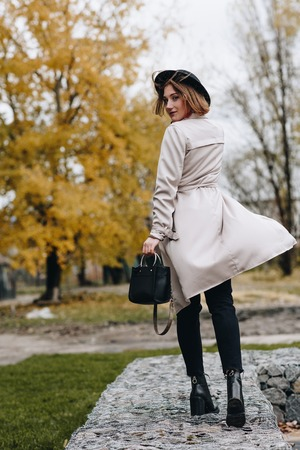 stylish woman in trench coat and hat walking by autumn park and turning back