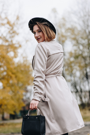 beautiful stylish woman in trench coat and hat walking by autumn park and turning back Stok Fotoğraf