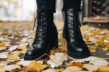 cropped shot of woman in fashionable leather boots standing on road covered with fallen leaves Stock Photo