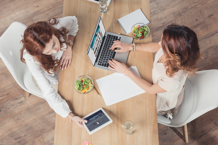 top view of young buisnesswomen having lunch together and using devices at office