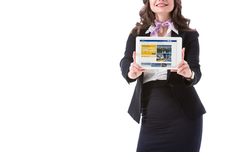 cropped image of stewardess holding tablet with booking website isolated on white